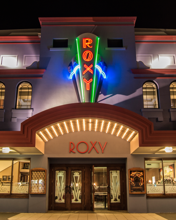 Photo of the Roxy Cinema building lit up at night.